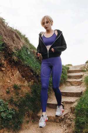 beautiful jogger running on stairs, Etretat, France