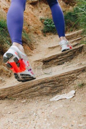 vue partielle de fille athlétique en chaussures de sport en cours d'exécution dans les escaliers, Etretat, France