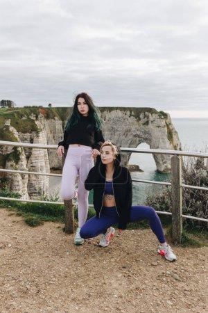 beautiful sportswomen posing in stylish sportswear on cliff, Etretat, Normandy, France