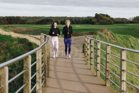 athletic women jogging on road with railings, Etretat, Normandy, France