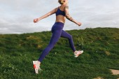 athletic girl in stylish sportswear jumping on green grass, Etretat, France