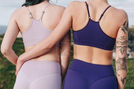 back view of sportswomen hugging in stylish sportswear, Etretat, Normandy, France