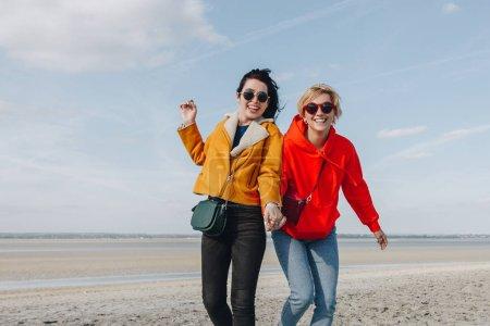 smiling female friends on sandy beach, Saint michaels mount, Normandy, France