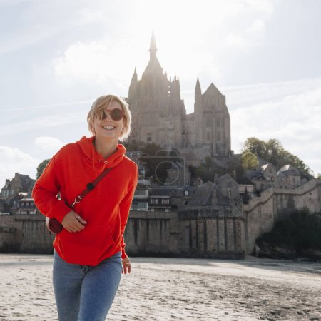 beautiful cheerful girl in red hoodie posing near Saint michaels mount, France