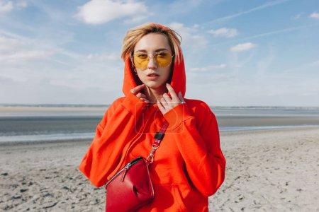 beautiful girl in red hoodie standing on beach, saint michaels mount, France