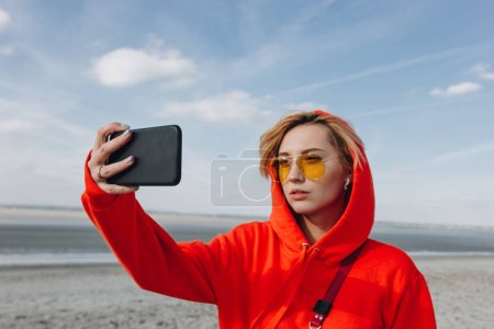 attractive girl in sunglasses taking selfie on smartphone on beautiful beach, saint michaels mount, France