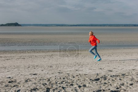 stylish young woman running on sandy beach, Saint michaels mount, France