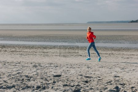 stylish girl running on sandy beach, Saint michaels mount, France