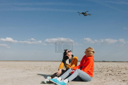 stylish girls sitting on beach and looking at drone, Saint michaels mount, Normandy, France