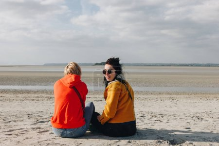 rear view of tourists sitting on sandy beach, Saint michaels mount, Normandy, France