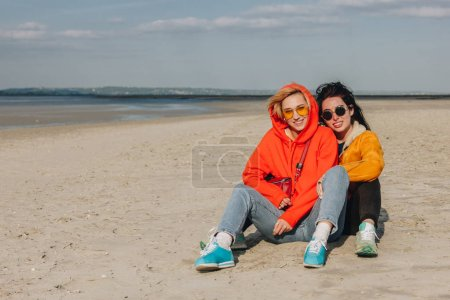 happy girls hugging on sandy beach, Saint michaels mount, Normandy, France