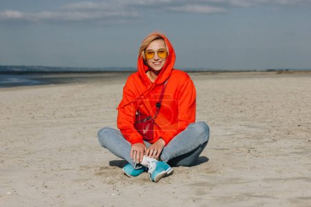 beautiful smiling girl in red hoodie sitting on beach, saint michaels mount, France