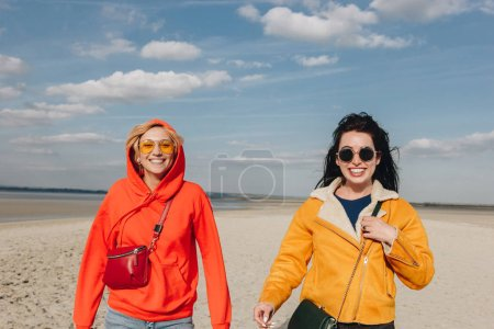 happy girls walking on sandy beach, Saint michaels mount, Normandy, France