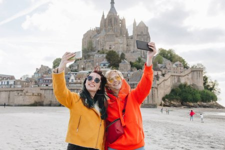 smiling tourists taking selfie on smartphone near Saint michaels mount, Normandy, France