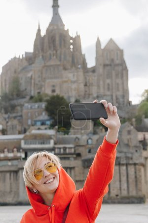 Happy girl taking selfie on smartphone near Saint michaels mount in Normandy, France