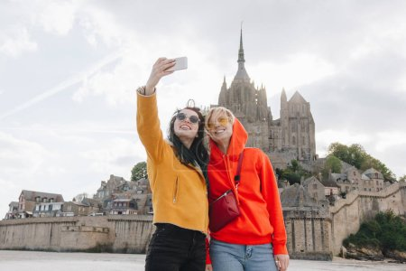 Photo for Beautiful girls taking selfie on smartphone near Saint michaels mount, Normandy, France - Royalty Free Image