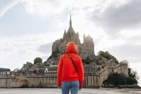 back view of girl in red looking at Saint michaels mount in Normandy, France