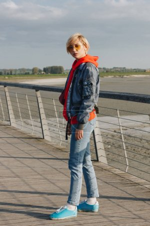 full length view of beautiful stylish girl in denim clothes and sunglasses looking at camera at sunny day, mont saint michel, france