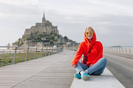 happy young woman smiling at camera while sitting near mont saint michel, france