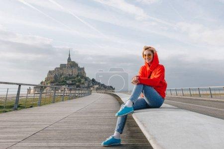Foto de Hermosa niña feliz en gafas de sol sonriendo a la cámara mientras que se sentaba cerca de mont saint michel, Francia - Imagen libre de derechos