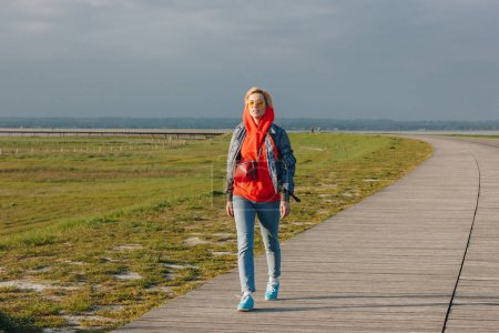 full length view of beautiful young woman in sunglasses walking on wooden walkway at sea coast