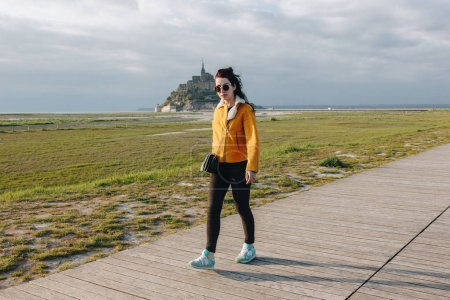 full length view of beautiful girl in sunglasses walking near mont saint michel, france