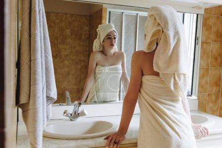 Photo pour Vue arrière du MoMA hubava dans des serviettes en regardant miroir dans salle de bain - image libre de droit