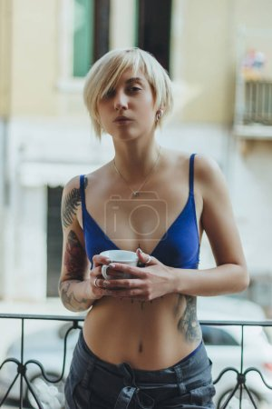 beautiful girl in bra standing on balcony with cup and looking at camera