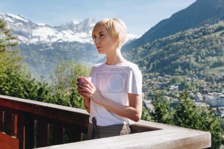 young woman holding cup and looking away while standing on balcony with beautiful mountains behind, mont blanc, alps