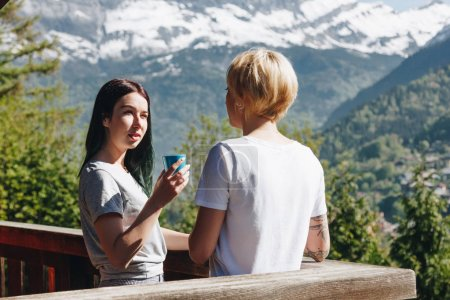 young women drinking tea and looking at each other while standing on balcony in beautiful mountains, mont blanc, alps