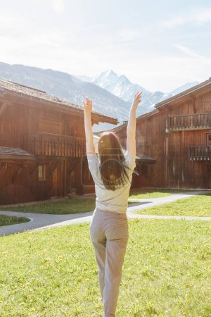 back view of beautiful young woman raising hands while standing between wooden houses in mountain village, mont blanc, alps