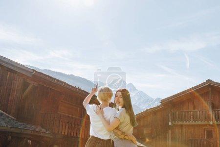 Photo pour Vue arrière de jeunes copines embrassant et regardant de belles montagnes, mont blanc, Alpes - image libre de droit