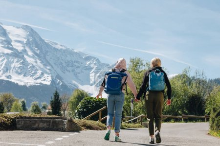 back view of girls with backpacks holding hands and walking on mountain road, mont blanc, alps
