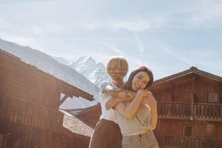 Photo pour Belles filles heureuses embrassant tout en se tenant entre des maisons en bois dans le village de montagne, mont blanc, Alpes - image libre de droit