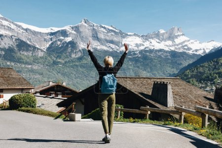 back view of girl with backpack raising hands and walking in scenic mountain village, mont blanc, alps