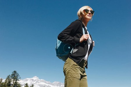 Photo for Low angle view of young woman in sunglasses with backpack looking away in mountains, mont blanc, alps - Royalty Free Image