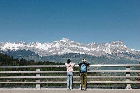 back view of girls standing near fence and looking at majestic snow-capped mountains, mont blanc, alps