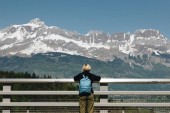 rear view of young woman with backpack looking at majestic snow-capped mountains, mont blanc, alps