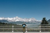 back view of girl with backpack looking at majestic snow-capped mountains, mont blanc, alps