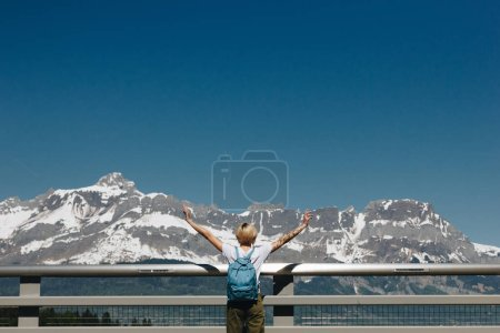 back view of girl with backpack raising hands and looking at majestic snow-covered mountains, mont blanc, alps