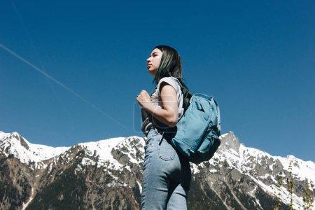 Photo pour Jolie jeune femme avec sac à dos debout dans les montagnes majestueuses enneigées, mont blanc, Alpes - image libre de droit