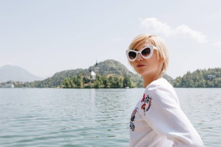 beautiful young woman in sunglasses standing near scenic lake in mountains, bled, slovenia