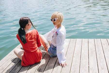 high angle view of two stylish girls in sunglasses sitting on wooden pier and looking at each other