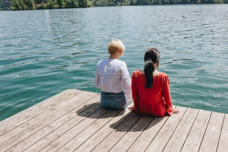 back view of two young stylish women sitting on wooden pier at lake, bled, slovenia