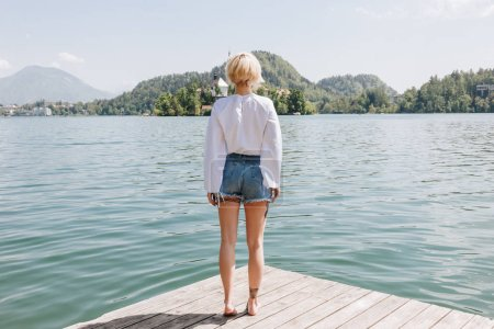 Photo for Back view of young woman standing on wooden pier and looking at scenic mountain lake, bled, slovenia - Royalty Free Image