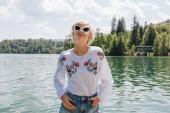 """Постер, картина, фотообои """"красивая молодая женщина в солнцезащитные очки, стоя возле живописной тихой горное озеро, Блед, Словения"""""""
