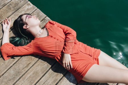 top view of beautiful stylish girl in sunglasses lying on wooden pier near lake
