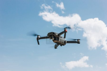 Photo for Controlled modern drone flying in blue sky - Royalty Free Image