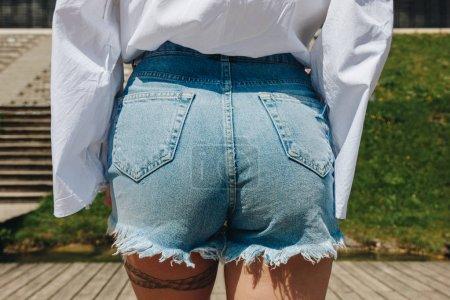 cropped shot of beautiful female buttocks in stylish denim shorts