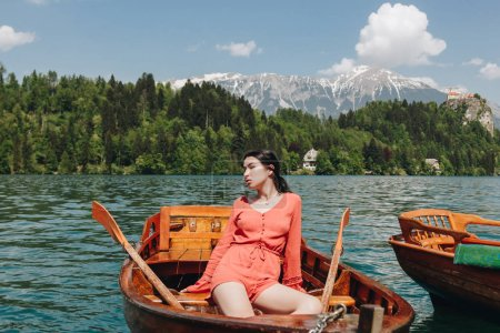 beautiful young woman sitting in boat at scenic tranquil mountain lake, bled, slovenia
